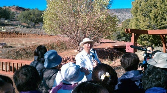 Ilchi Lee speaking to a meditation group at Sedona Mago Retreat in the Healing Garden