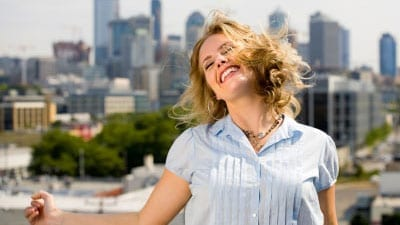 happy woman with a city in the background