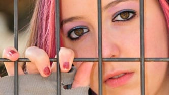 young girl with pink hair behind fence