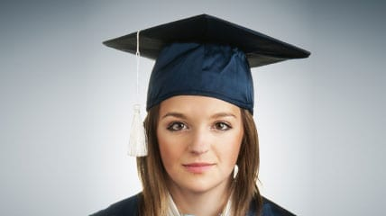 young woman in a graduation cap and down with a globe floating between her hands