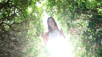 Girl in woods with sun shining on her