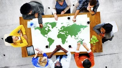 Diverse group of people sitting at a table with a map of the earth