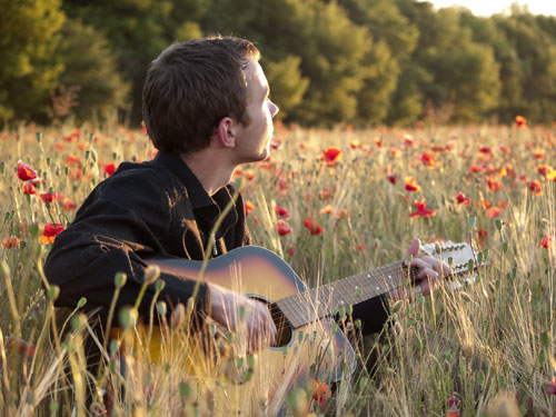 Man playing a guitar in a field
