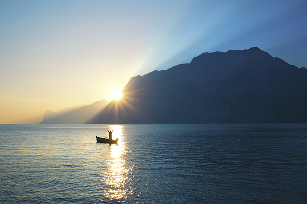 woman cheering in a boat while the sun comes over the mountain