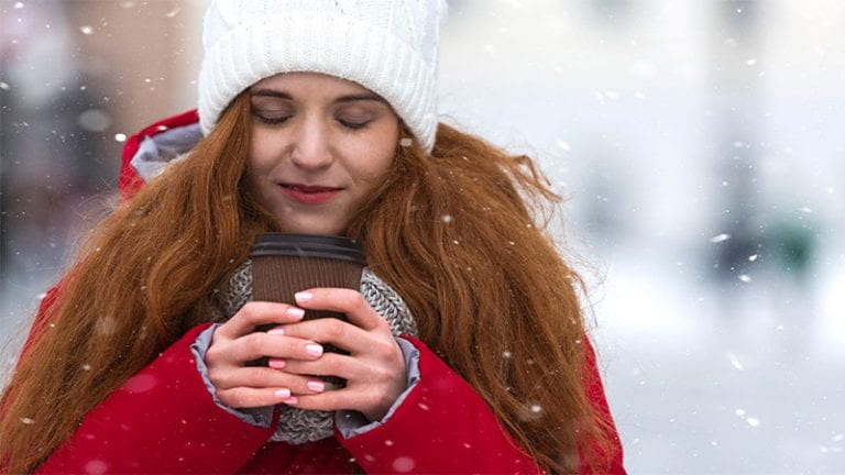 Girl in the snow holding hot coffee