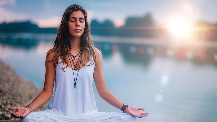 woman in white shirt meditating by a lake