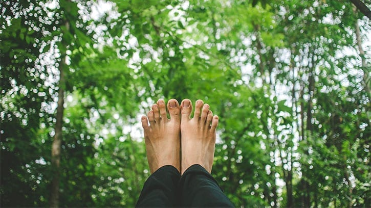 Feet over a backdrop of trees