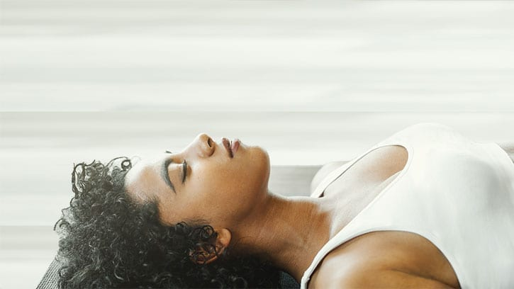 woman breathing on yoga mat