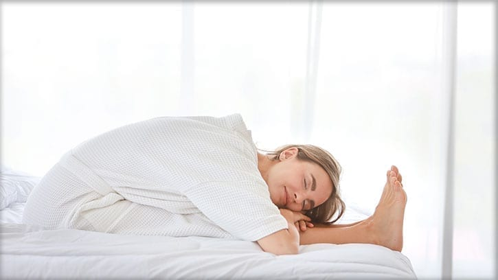 woman stretching on a bed