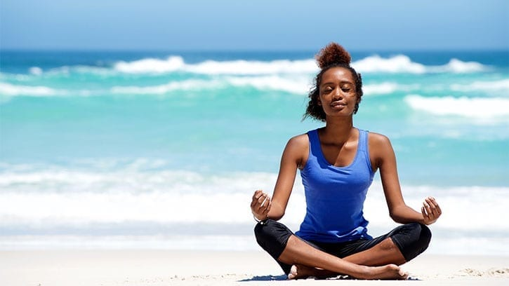 Young Black woman meditating on a beach