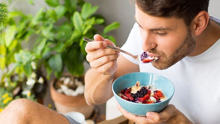 White man eating cereal with berries outdoors