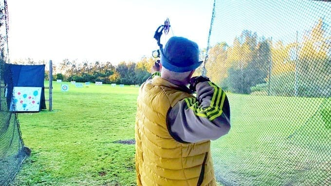 Ilchi Lee shooting a bow and arrow