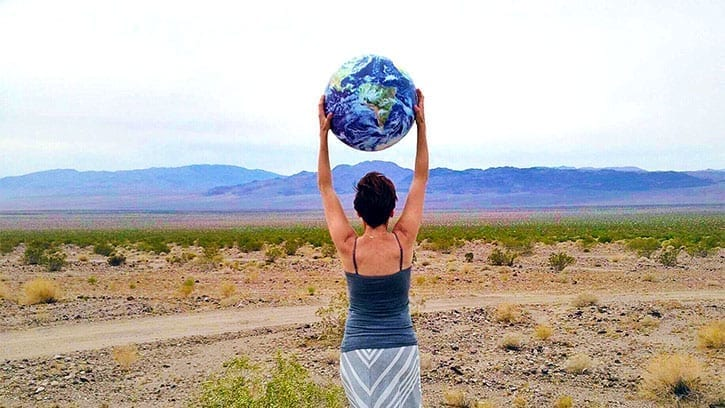 woman holding a globe over her head in the desert