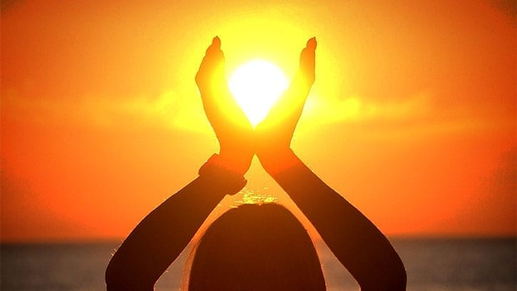 silhouette of woman with hands enclosing the setting sun