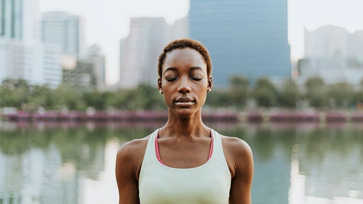 black woman meditating in front of a lake and cityscape