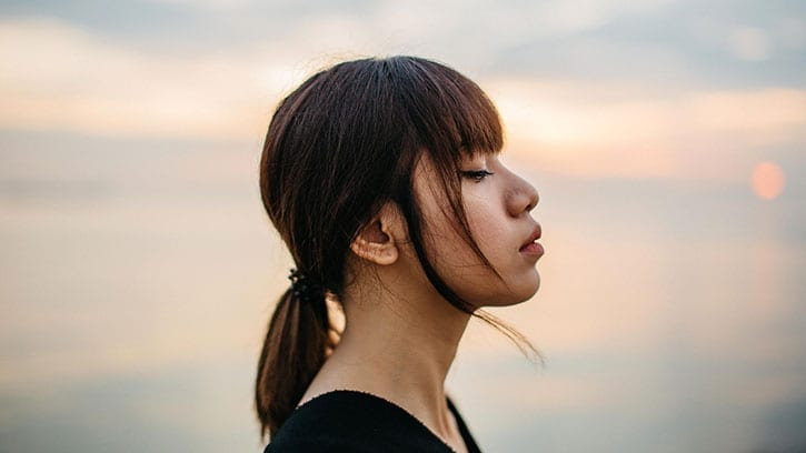 young woman closing her eyes to the setting sun