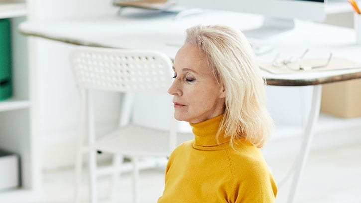 older woman meditating in her home office