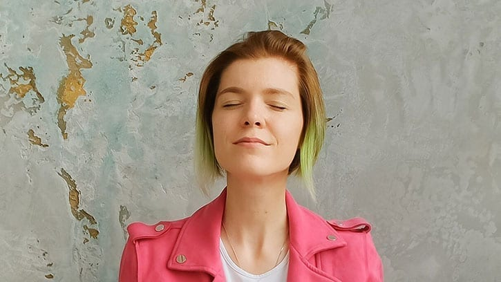 Woman with green-tipped hair and bright pink jacket meditating against a gray wall