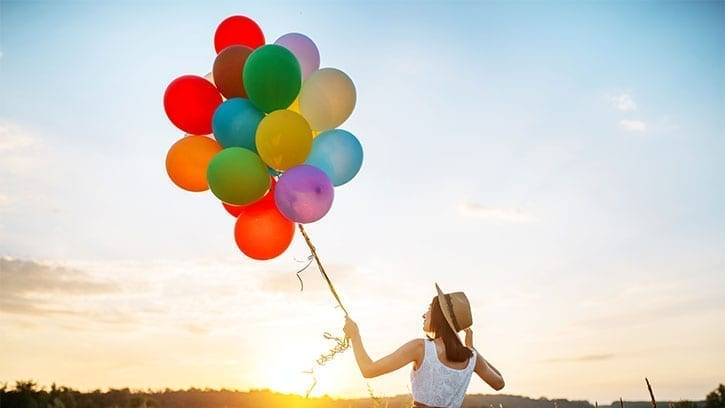 woman holding many balloons