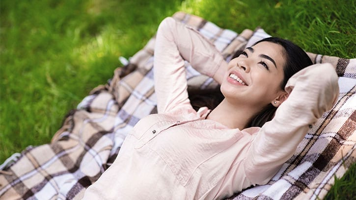 Asian woman lying in the grass