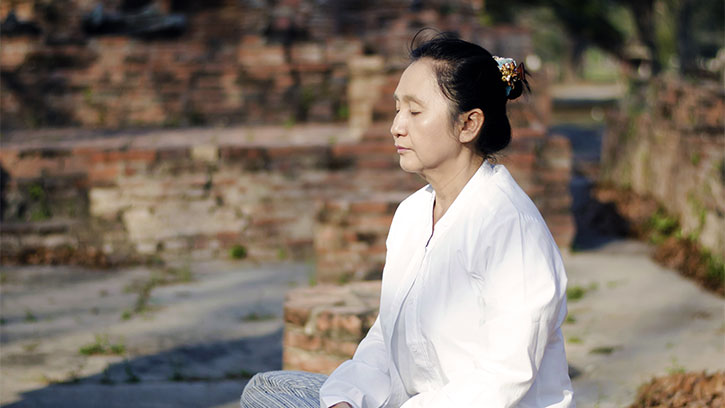 middle aged Asian woman meditating
