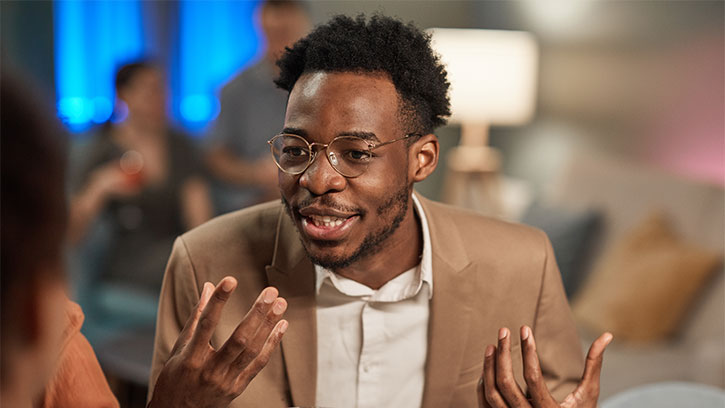 young black man speaking with a smile and gesturing with his hands