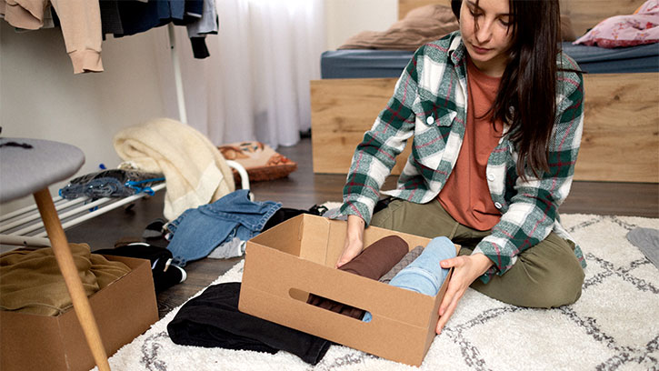 woman putting away clothes in body
