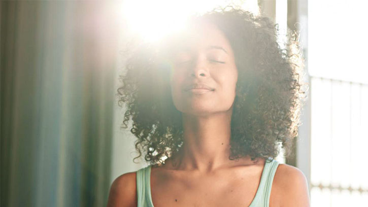 woman meditating with sunlight behind her head